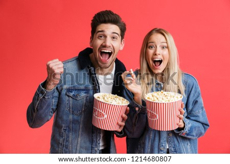 Portrait of an excited young couple dressed in denim jackets standing together isolated over red background, watching movie, eating popcorn #1214680807
