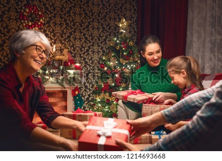 Merry Christmas and Happy Holidays! Grandma, mum, dad and child exchanging gifts. Parents and daughter having fun near tree indoors. Loving family with presents in room. #1214693668