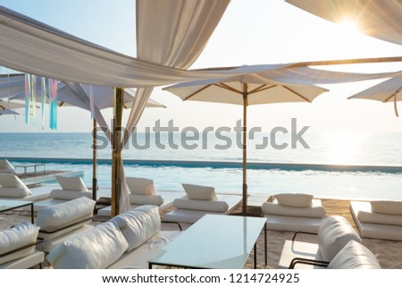 Beautiful luxury swimming pool on sea view and umbrella and chair in hotel resort with sunset time #1214724925