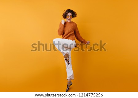 Full-length photo of elegant european female model dancing with excitement. Studio shot of slim brunette girl in white pants jumping with happy face expression. #1214775256