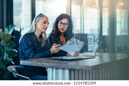 Two business woman sitting at a table and working together. Senior executive showing her phone and papers to young colleague at office. #1214785399