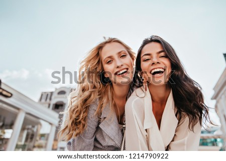 Inspired laughing ladies posing together on sky background. Outdoor photo of interested caucasian sisters enjoying good day.