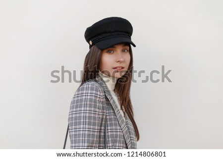 Fashionable portrait of a beautiful young girl in elegant clothes near the wall on the street #1214806801