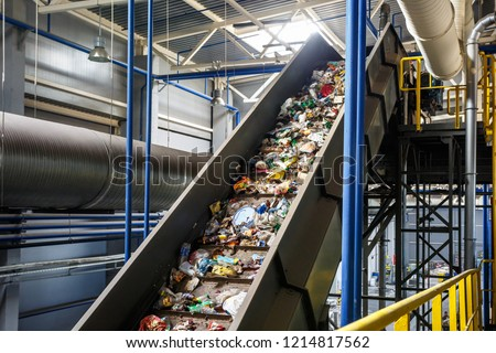 moving conveyor transporter on Modern waste recycling processing plant. Separate and sorting garbage collection. Recycling and storage of waste for further disposal.  Royalty-Free Stock Photo #1214817562