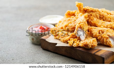 Breaded chicken strips with two kinds of sauces and fried potatoes on a wooden Board. Fast food on dark brown background. with copy space Royalty-Free Stock Photo #1214906158