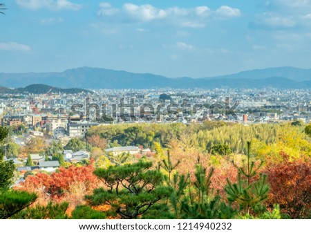 Arashiyama cityscape viewpoint with autumn tree forest under cloudy blue sky with mountains in background, Japan #1214940232