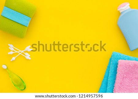 Children's personal care kit. Bath accessories with teeth brush on yellow background top view copy space #1214957596
