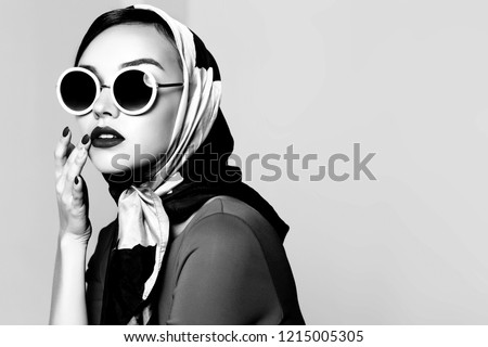 Young woman in retro style. Sunglasses and silk scarf. Sixties style fashion retro woman. Black and white image Royalty-Free Stock Photo #1215005305