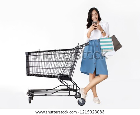 happy asian girl love shopping  with mobile shopping cart and shopping bag on white background. Teenage shopaholic concept #1215023083