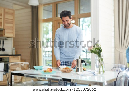 Happy excited young man with stubble wearing pajamas standing at table and setting it while preparing breakfast for wife in modern kitchen #1215072052
