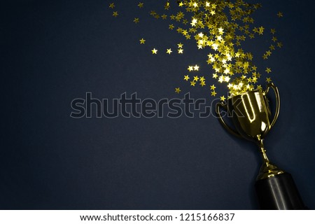 image of small gold cup, concept for winning or success Royalty-Free Stock Photo #1215166837