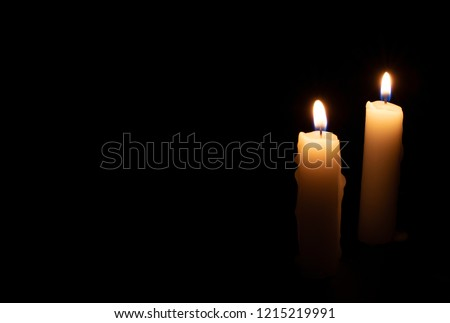 Two candles on black background. Lighting candles in darkness. Yellow wax candle with warm flame. In memoriam banner template with text space. Religious or mourning backdrop. Yellow candlelight photo