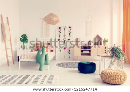 Boho kid's bedroom with white metal bed, wooden furniture and colorful poufs, real photo #1215247714