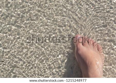 One female leg in the water. Sandy beach on the ocean. #1215248977