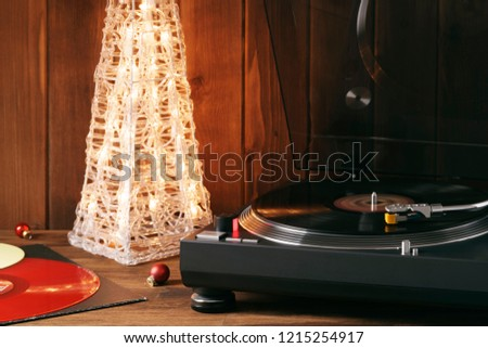 Christmas picture. Noel. The rotating moment of a red vinyl record on turntable, the stylus needle falls on vinyl, music on background of glowing Christmas tree with red glass balls. Copy space