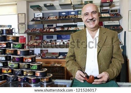 Portrait of a happy middle-aged tobacco shop owner with cans on display Royalty-Free Stock Photo #121526017