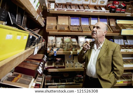 Small tobacco store owner looking at cigar boxes on display in shop Royalty-Free Stock Photo #121526308