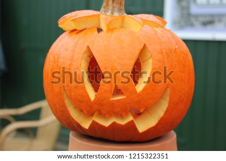 Pumpkin with a carved face in daylight #1215322351
