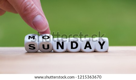Hand is turning dice and changes the word Sunday to Monday #1215363670