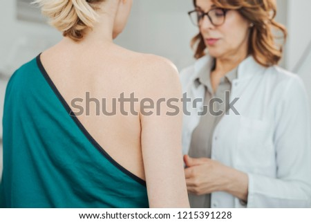 Woman gynecologist doing breast exam to her patient. #1215391228