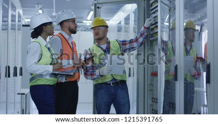 Group of multiethnic men and woman in hardhats working in hall of solar plant control center having discussion between racks Royalty-Free Stock Photo #1215391765