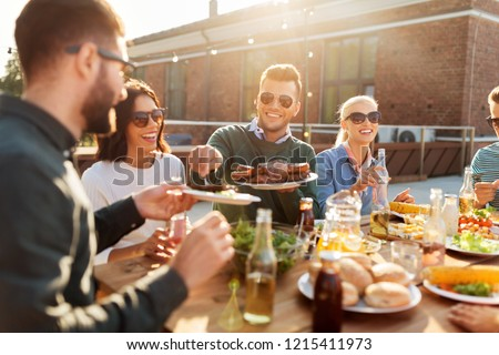 leisure and people concept - happy friends eating and drinking at barbecue party on rooftop in summer Royalty-Free Stock Photo #1215411973