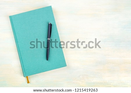 A photo of a teal blue journal with a pen, an elegant diary, notebook or planner, shot from above with copy space #1215419263