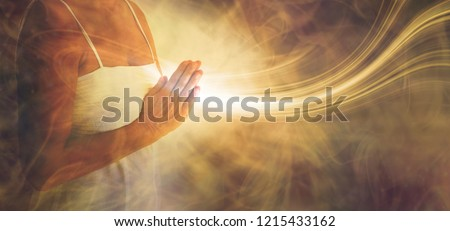 Peaceful prayer sending love and light out -  female in white dress with hands in prayer position and a stream or white light flowing outwards with a rustic golden brown ethereal energy background  Royalty-Free Stock Photo #1215433162