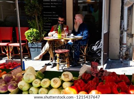 PARIS, FRANCE - SEPTEMBER 1, 2018: Beauvau street market. Two men sitting at cafe terrace at background. Parisian urban scene. #1215437647