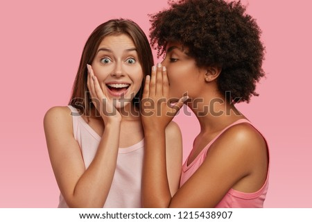 Young black woman whispers secret to her Caucasian friend, gossip together and spread rumours. Emotional European girl feels amazed to hear confidential information from companion. Secrecy, gossiping #1215438907