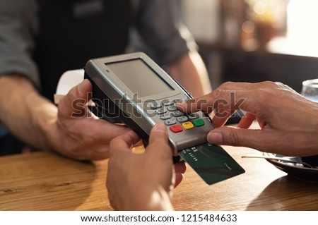 Closeup of hand using credit card swiping machine to pay. Female hand with credit card paying through terminal for payment in coffee shop. Woman entering debit card code in swipe machine. #1215484633
