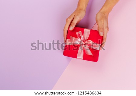 Woman holding gift box on color background #1215486634