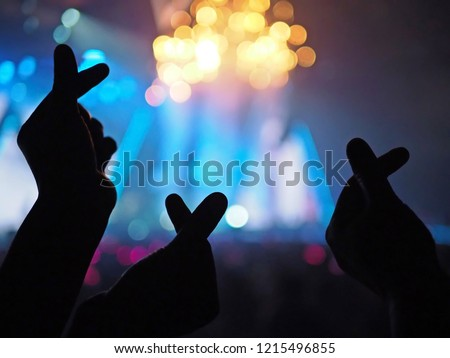 K-Pop music theme or Live concert background with silhouette hands of audience making mini heart shaped hand gesture for artist supporting over blurred audience and stage with lighting effects.