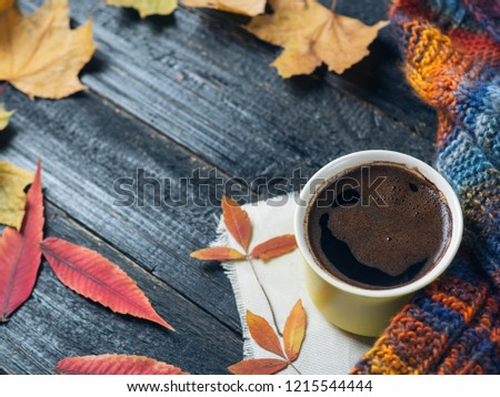 A mug of hot coffee on a dark wooden table with autumn leaves and a scarf. #1215544444