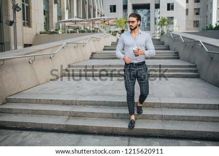 Picture of attractive young man walks on steps and looks to left. He holds cup of coffee in left hand. Guy wears sunglasses. He looks stylish.