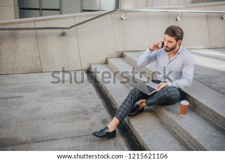 Picture of young businessman sits on steps and works. He talks on phone and looks at laptop's screen. Young man keeps his legs crossed.