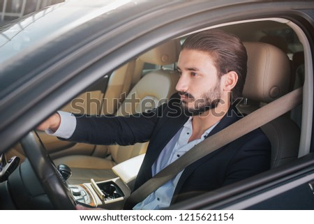 Picture of nice and confident businessman sitting in luxury car. He looks straight forward. Man poses. He has seat belt locked and oing across his body.