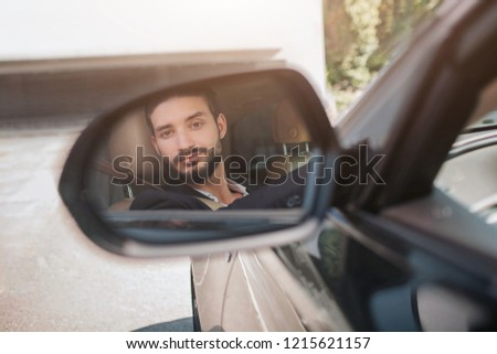 Picture of man sitting in car and looking at wing mirror. He sils a bit. Young man satisfied with his car. It is sunny outside.