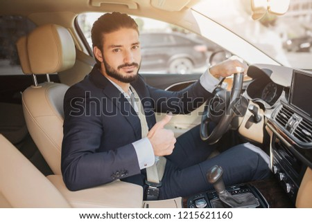 Nice picture of young businessman sitting in luxury car and holding big thumb up. He hold one hand on steering wheel. Young man recommends this car.