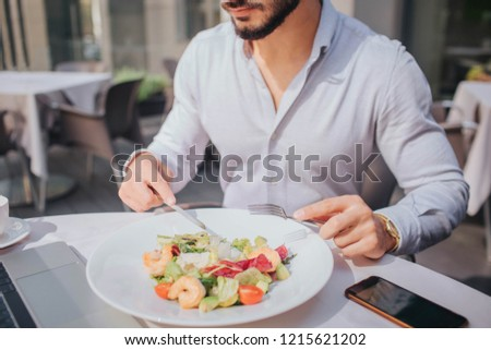 Cut view of bearded young man sitting at table and eating salad. There are laptop and phone on picture.