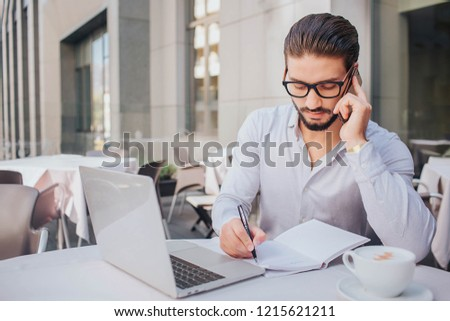 Picture of young man sitting at table and talking on phone. He is making notes in notebook and looks down. Businessman is serious and concentrated. There are laptop and cup of coffee at table.