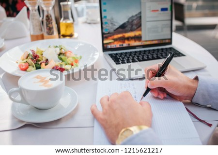 Nice picture of man's hands holding pen. There are laptop, salad and up of coffee at table. Businessman ordered food to eat. He is busy. There are opened notebbok at table.