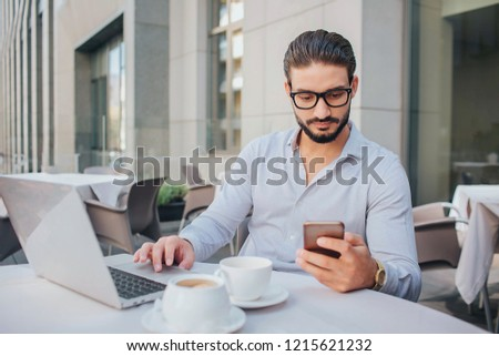 Picture of businessman sits at table and hold phone. He looks at it. Guy has two cups of coffee and laptop at table. He has some rest.