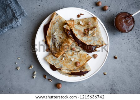 Crepes with chocolate spread and hazelnuts. Homemade thin crepes for breakfast or dessert. #1215636742