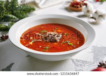 Macro Photo of Homemade Red Tomato Soup with Beef, Greens and Vegetables with Selective Focus. Rich Hot Veal Meat Broth with Tomatoes, Potatoes, Paprika in White Plate Close Up #1215636847