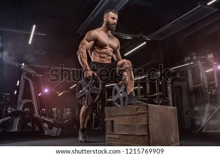 Attractive tall muscular bodybuilder doing heavy deadlifts in moder fitness center. #1215769909