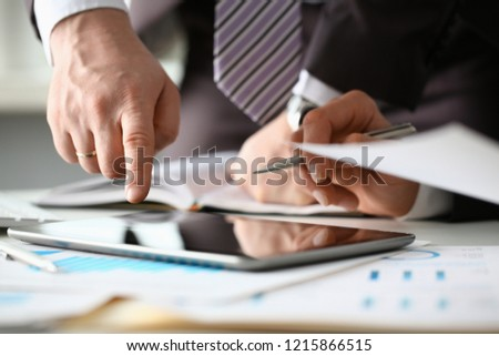 Two businessman are looking and studying statistics on tablet display closeup. Male hand opponent holds pen and points out problem collaboration business coach cooperation partnership palm concept #1215866515