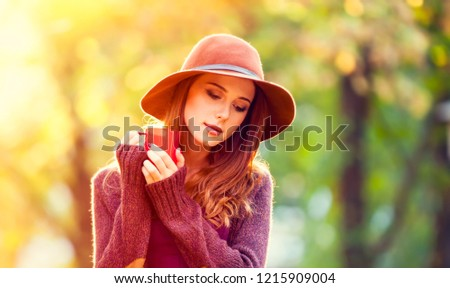 Redhead girl in hat and cup in the autumn park. #1215909004