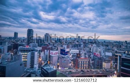 Hep Five, Hankyu, Osaka Prefecture, Japan - November 2018 : Osaka Futuristic cityscape skyline from red Ferris Wheel on the top of building on winter sky #1216032712