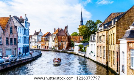 Brugge/Belgium - Sept. 18 2018: Canal boat ride on the St. Annarei canal in the historic city of Bruges, Belgium with the steel Lanchals sculpture and the tower of the St. Anna Church on the right #1216079797
